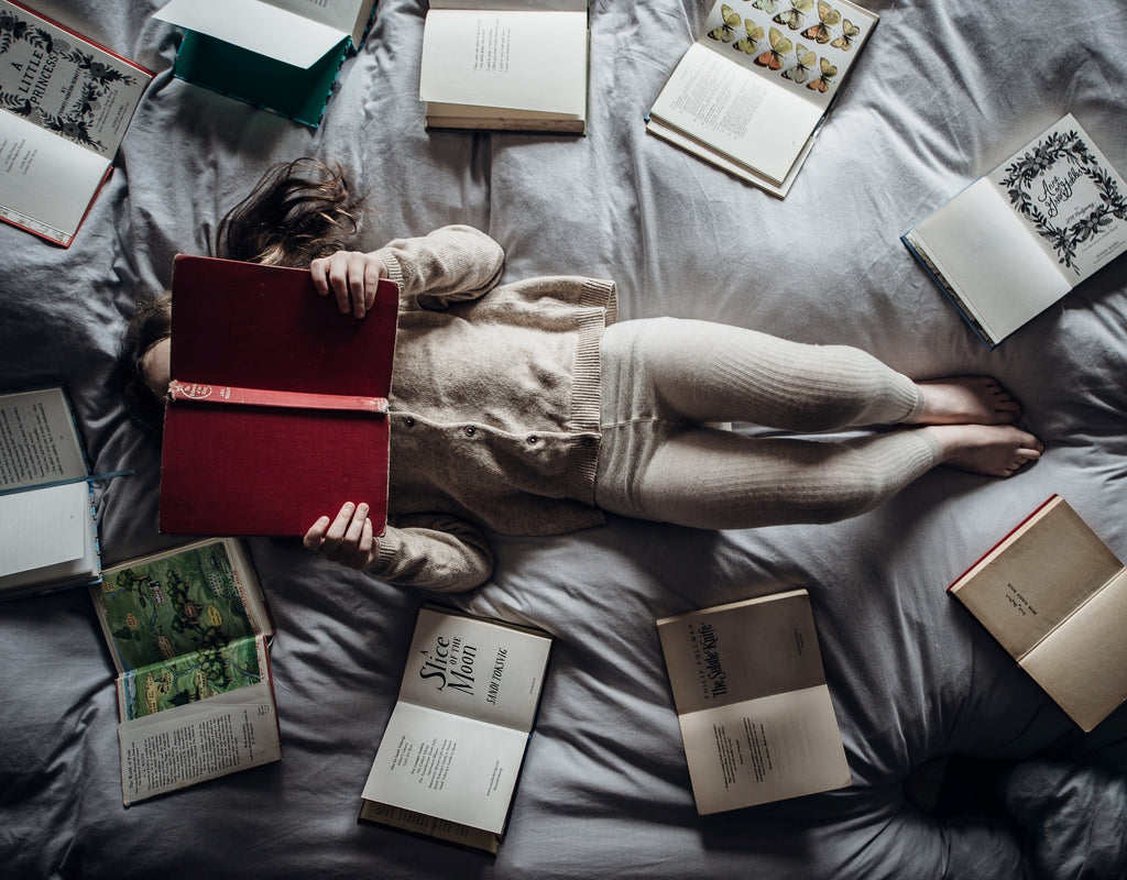 Young lady reading laying down on her bed while surrounded by opened books