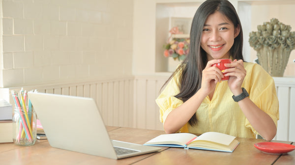 asian woman with a laptop working at home to prevent the spread of coronavirus