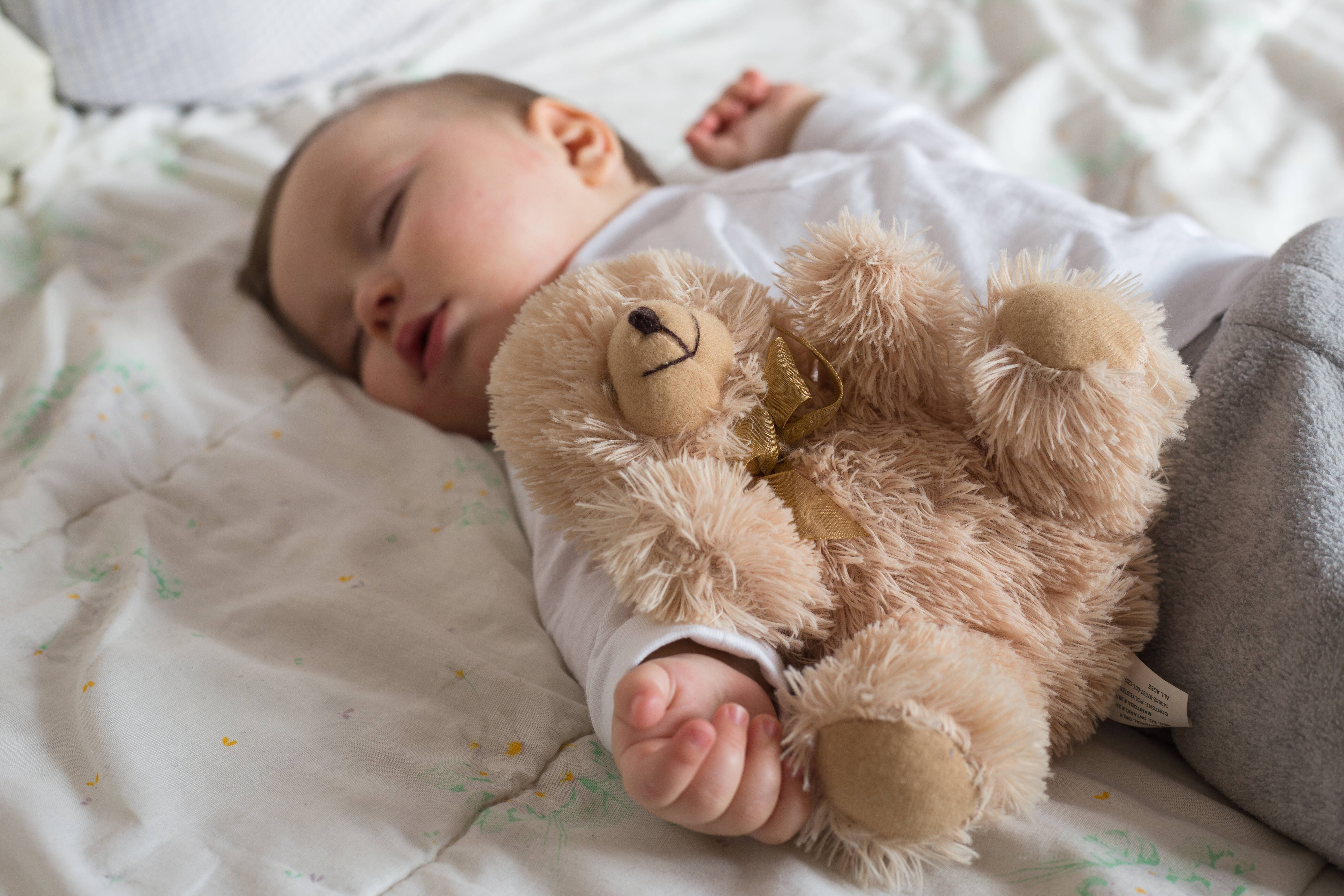 Baby sleeping in bed with a teddy bear