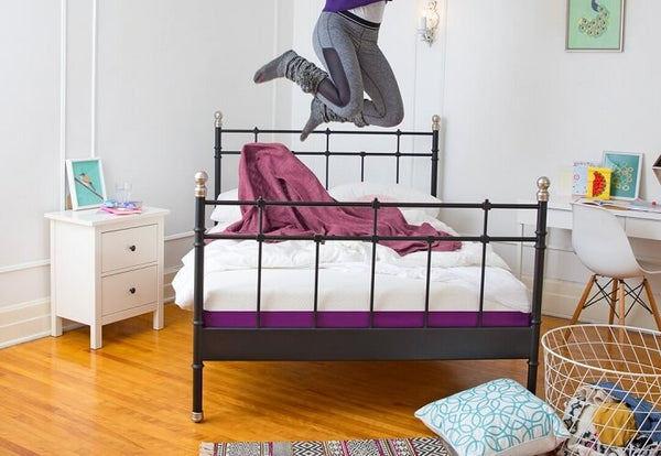 A person jumps on the Polysleep Mattress in a room