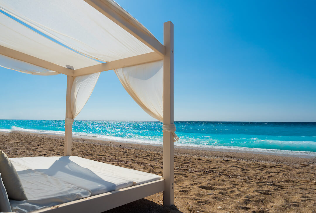 A canopy bed parked on an oceanfront beach