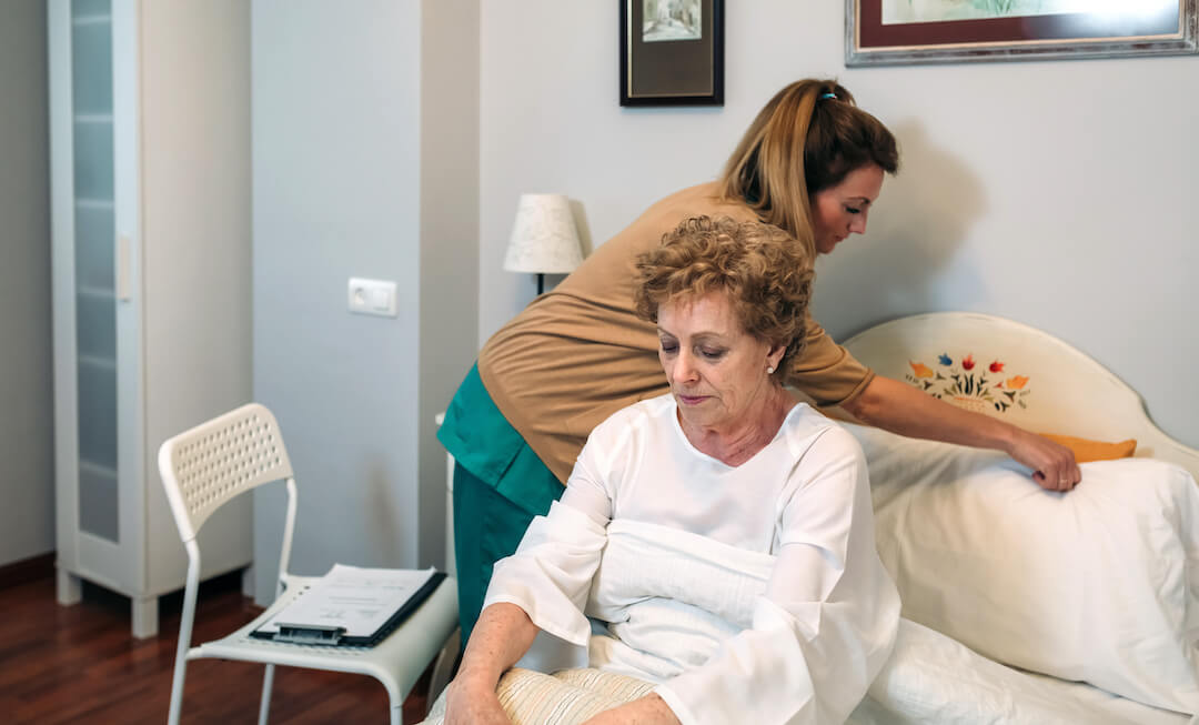 Home caregiver installs an accommodating pillow for the elderly woman in her bed