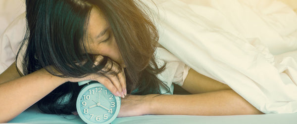 Woman sleeping on top of her alarm clock.