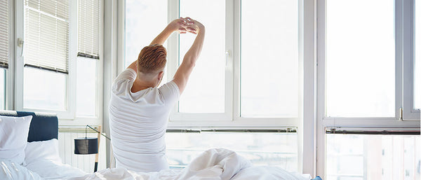 Man stretching his arms before getting out of bed.