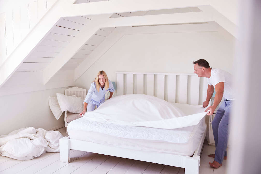 A couple placing the fitted sheet on their mattress