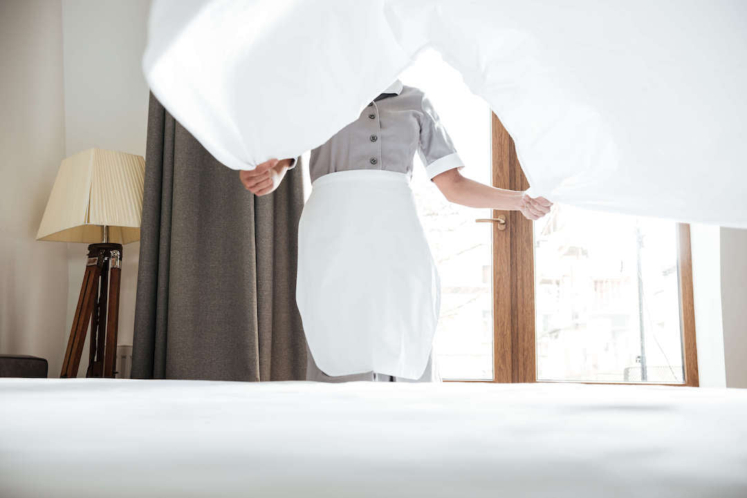 A maid placing a mattress sheet on the bed