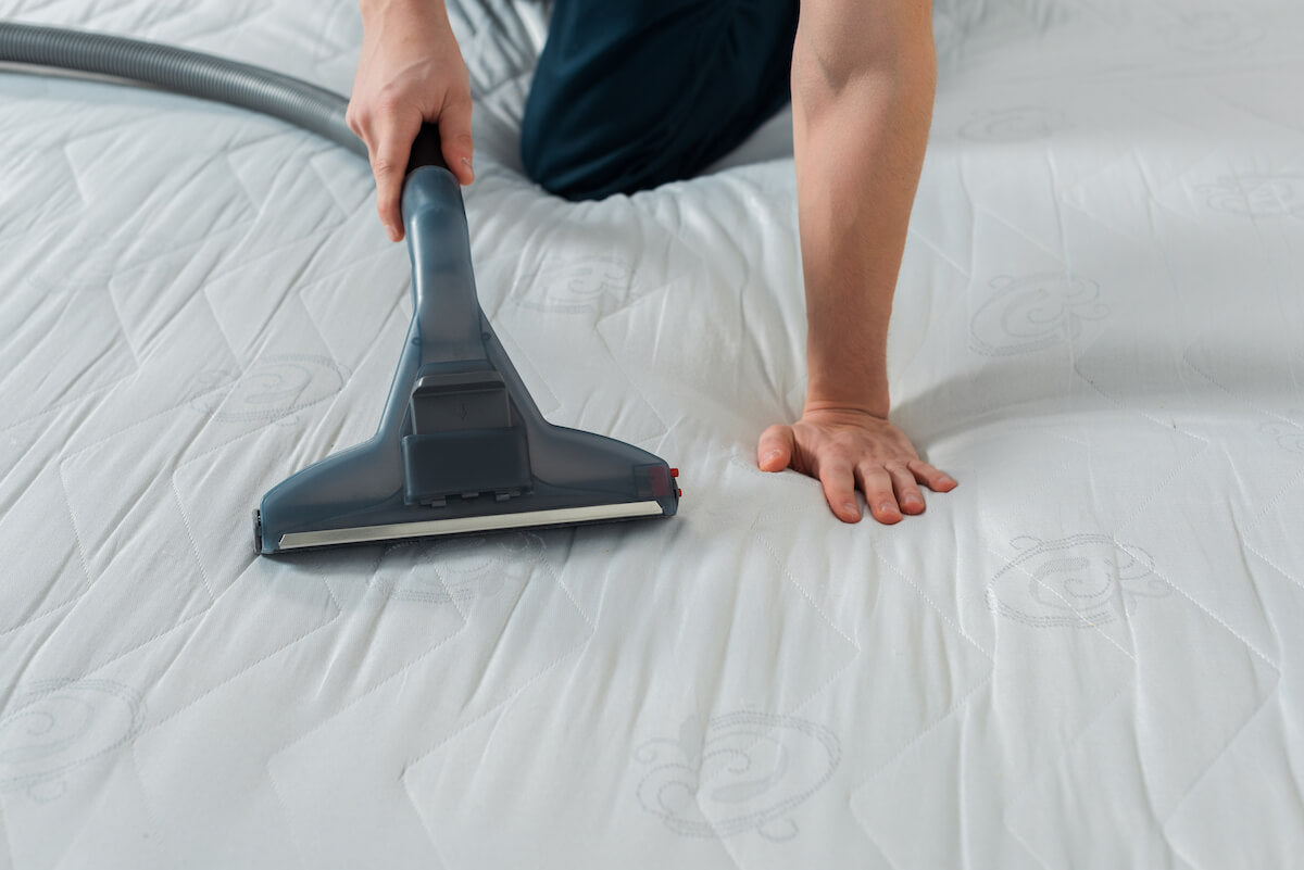 A cleaner performs cleaning of a white mattress with a vacuum cleaner