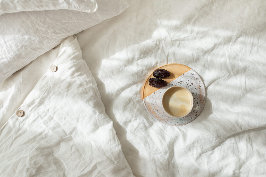 A cup of fresh coffee on a ceramic tray in bed