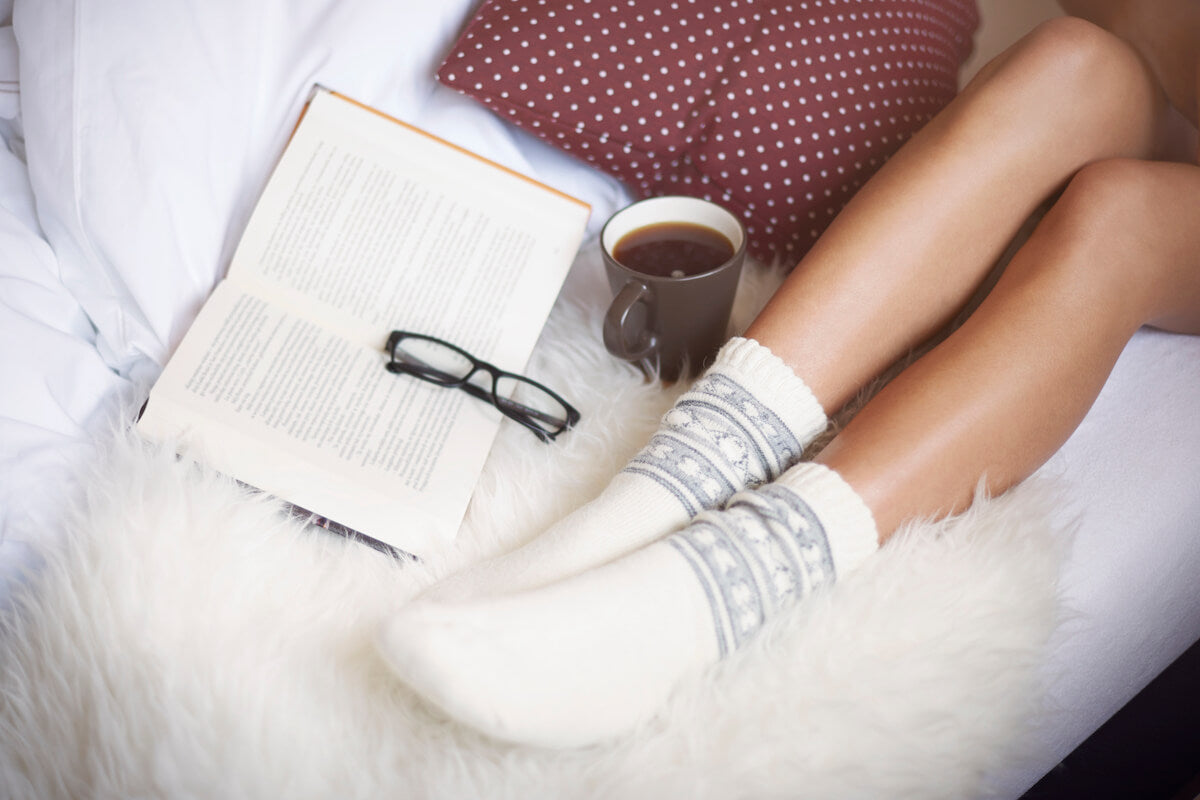 The low-raised legs of a woman on a white foam cushion including her coffee and her book