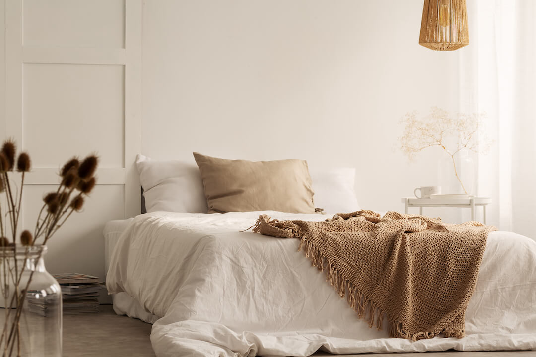 Flowers, a lamp and a bed in a white color room