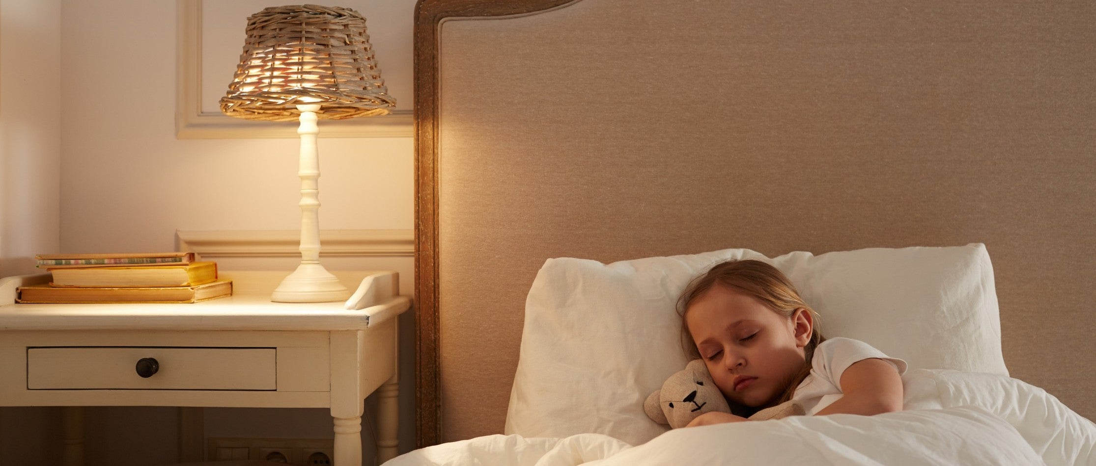 Little girl sleeping in bed with her teddy bear and bedside night on.