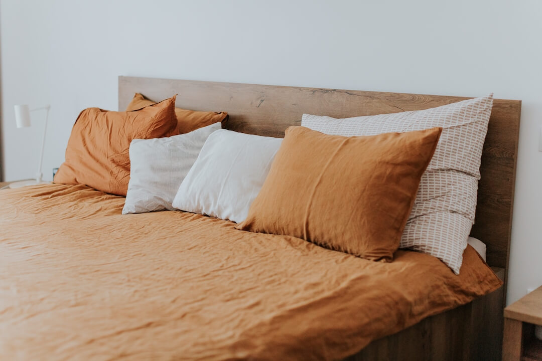 A bed with orange linen bed sheets