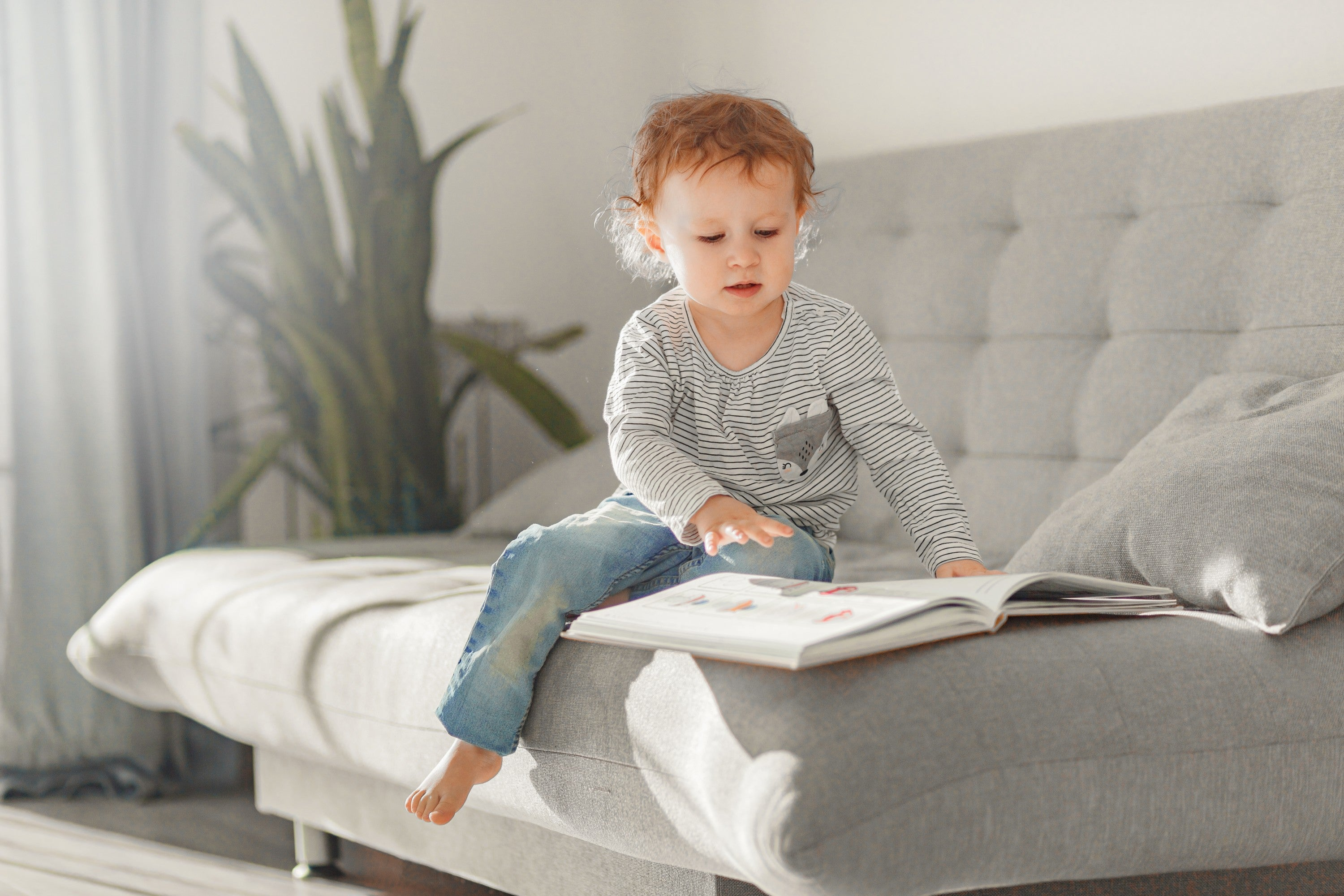 2 year old little girl reading a book on a bed