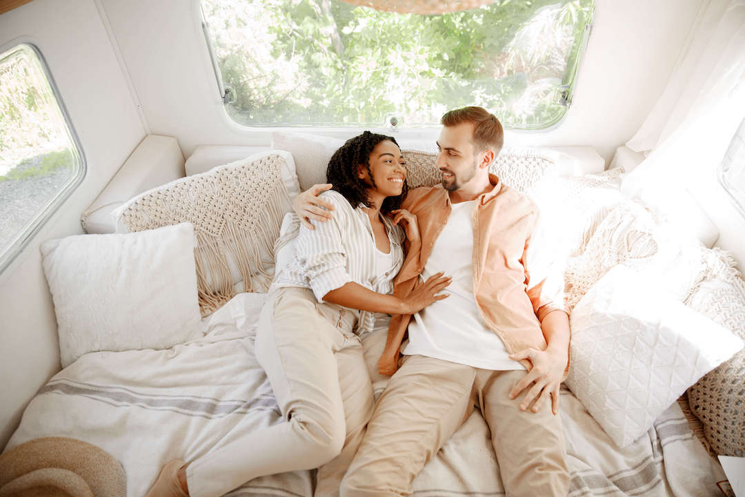 A smiling couple lying on their trailer bed