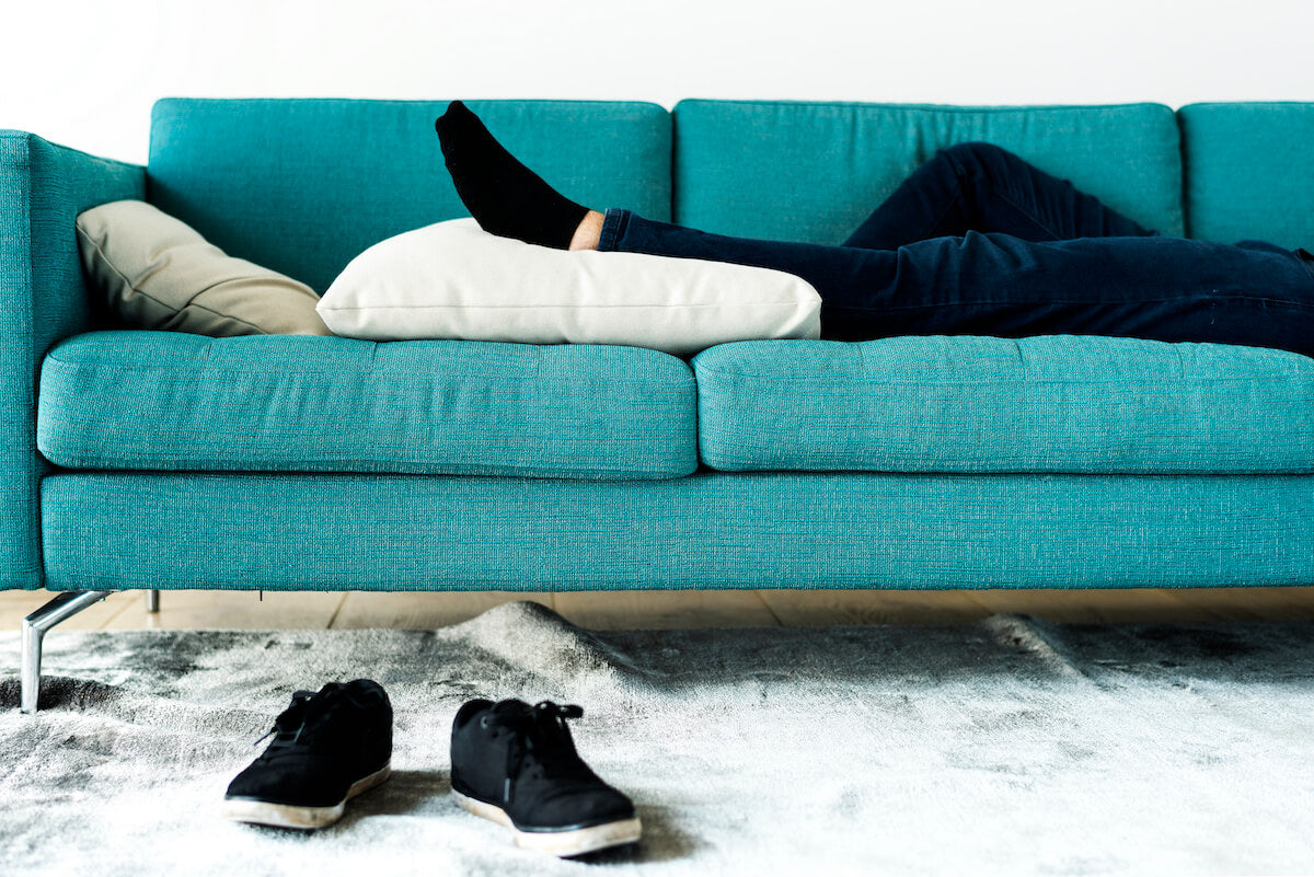 A man lying on a sofa with his legs low on the pillow