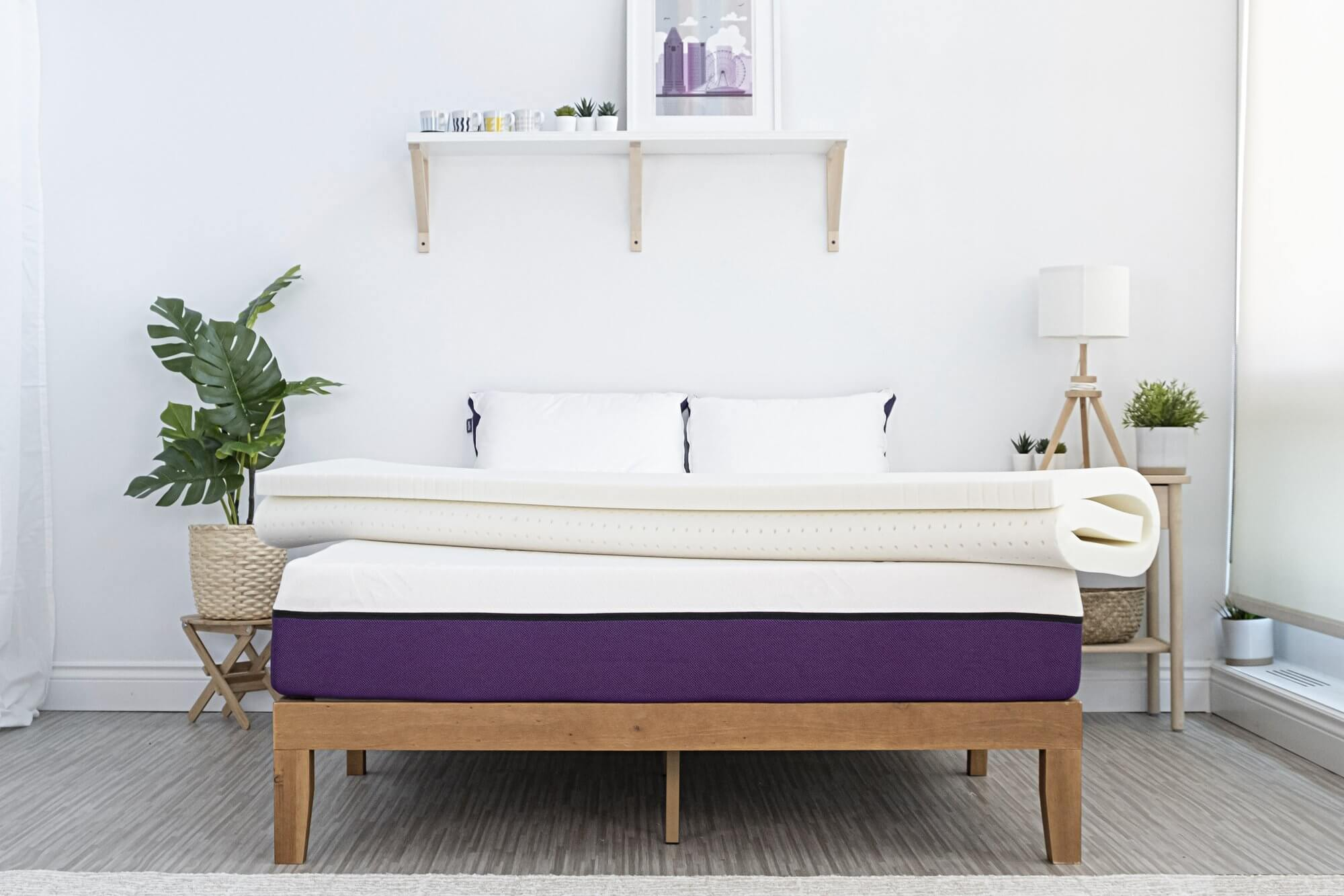 The Polysleep mattress topper fully rolled up on the Polysleep bed