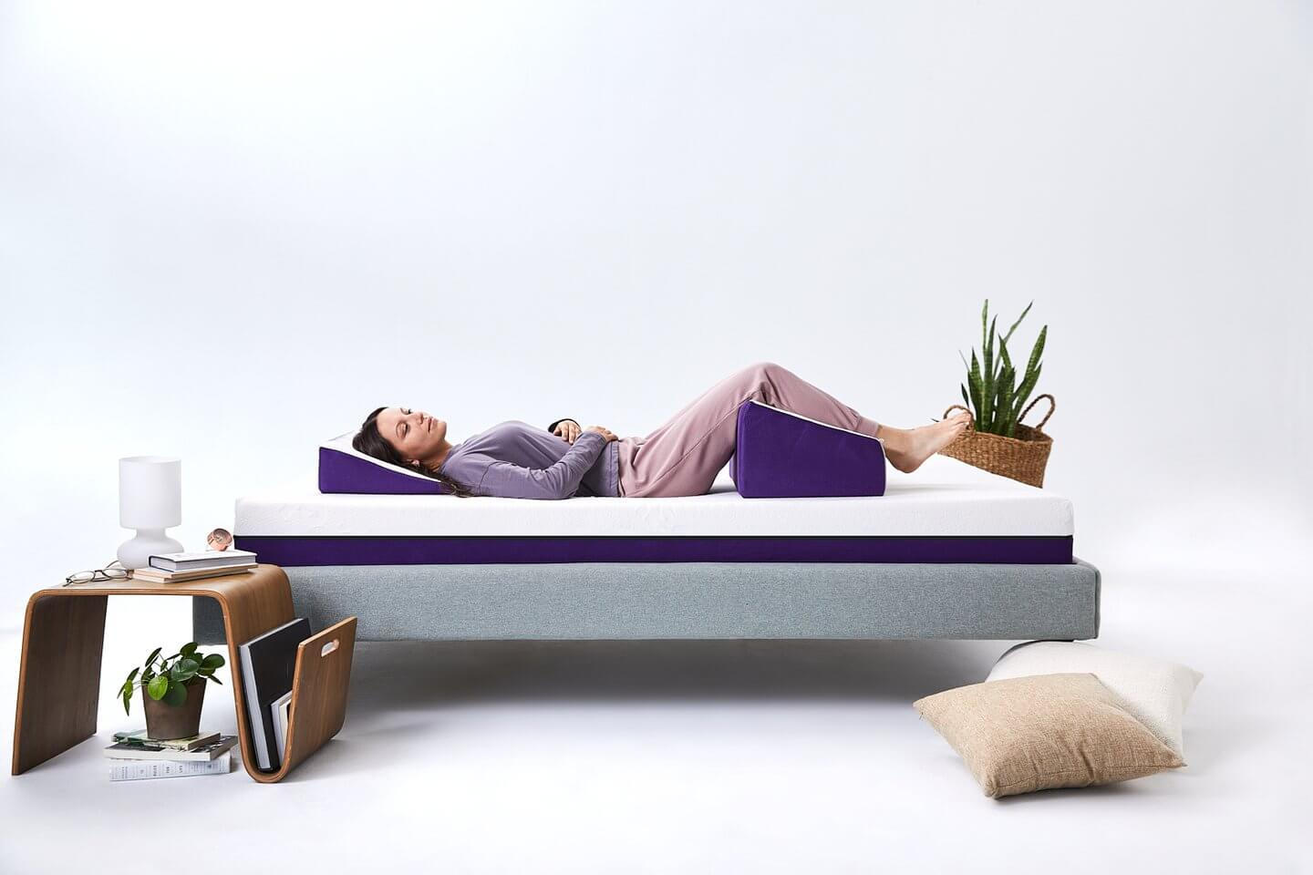 Woman lying with her legs elevated on the Polysleep wedge pillow