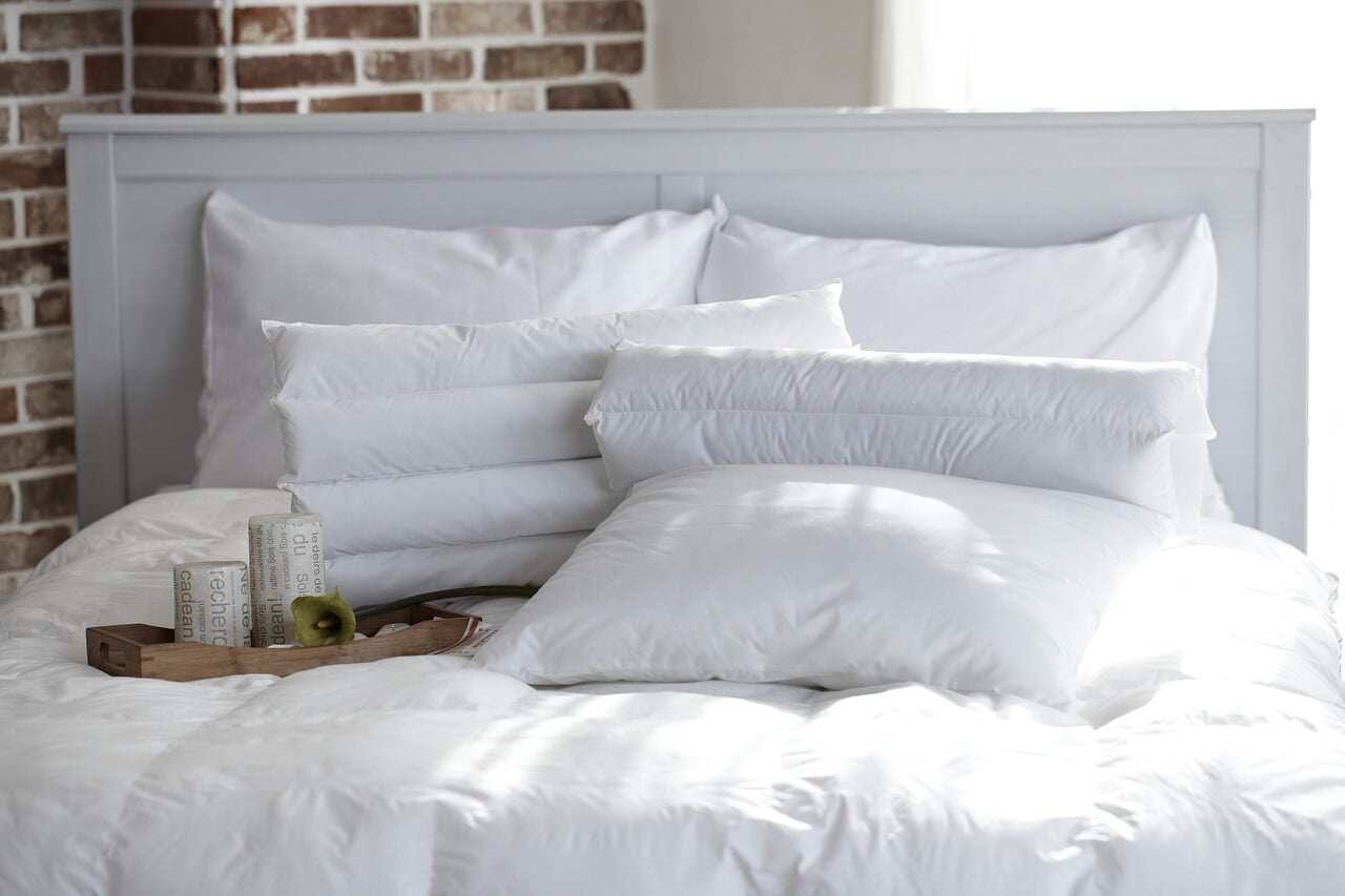 A clean bed with its set of sheets and pillows