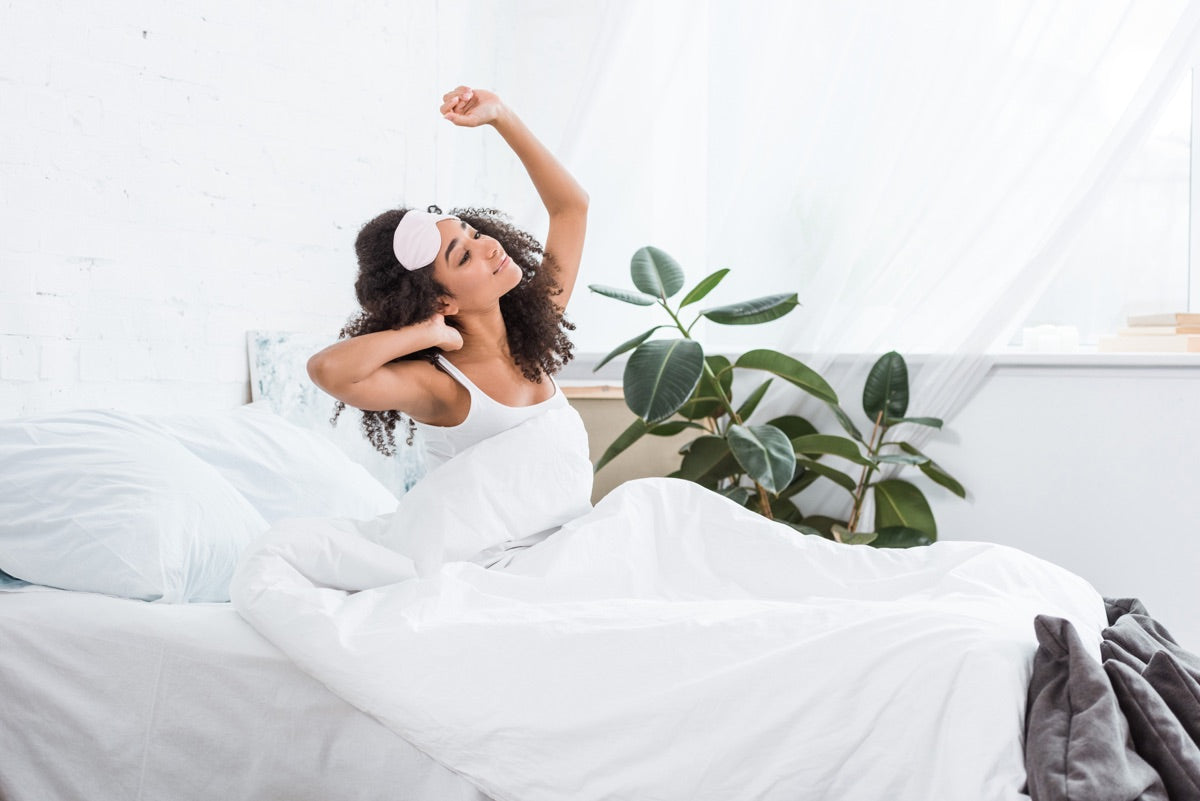 Side view of a young woman stretching at sunrise in the morning