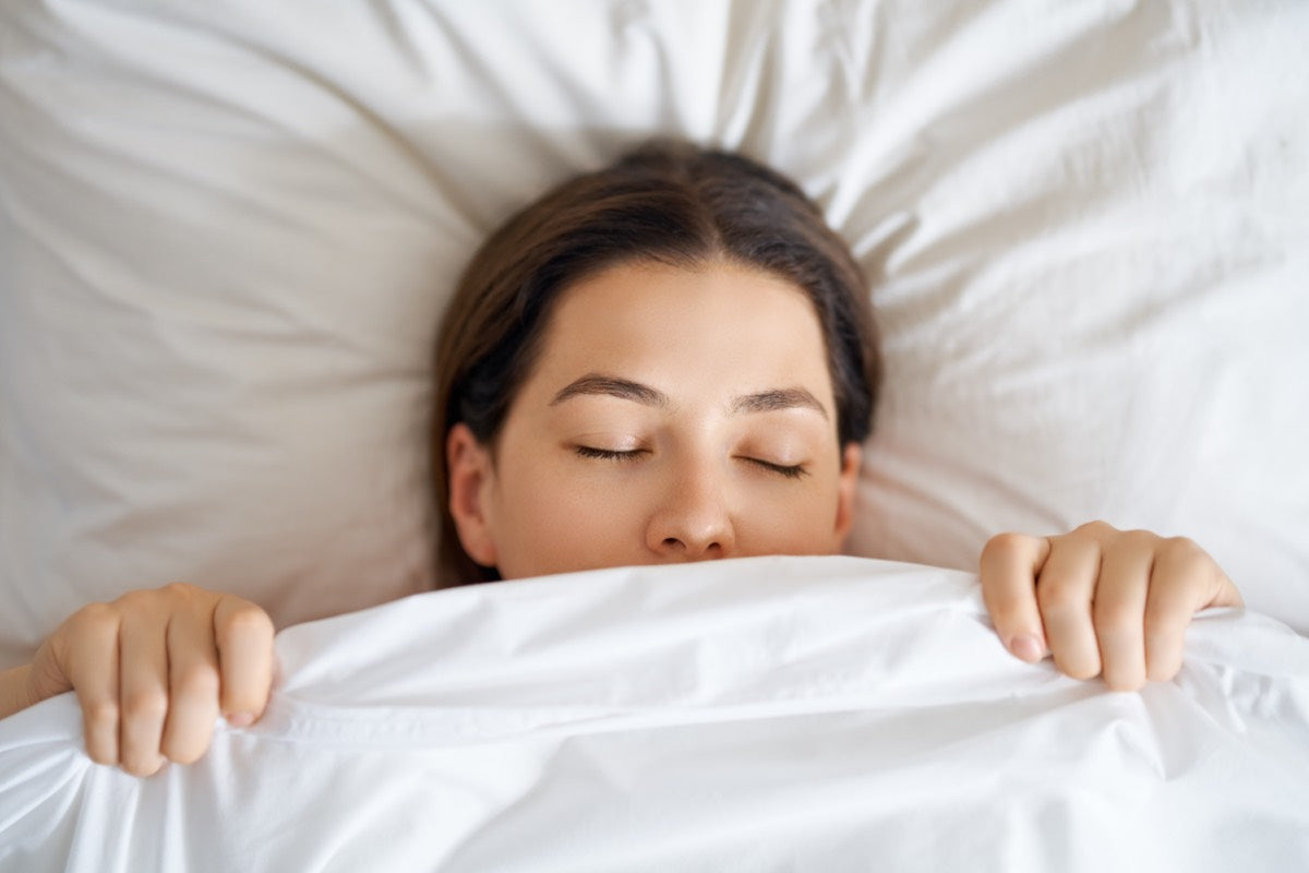 Woman sleeping with her mouth hidden by her blanket in her bed