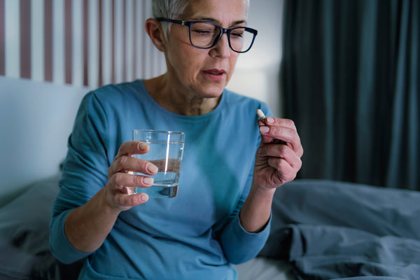 sleepless senior woman suffering from insomnia holding glass of water