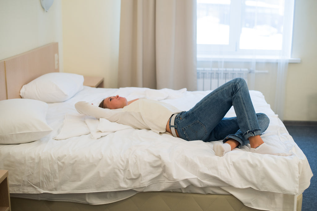 Tired woman is lying in bed with her arm on head