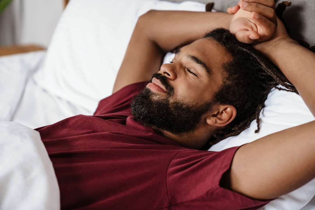 Man sleeping in bed without suffering from allergies