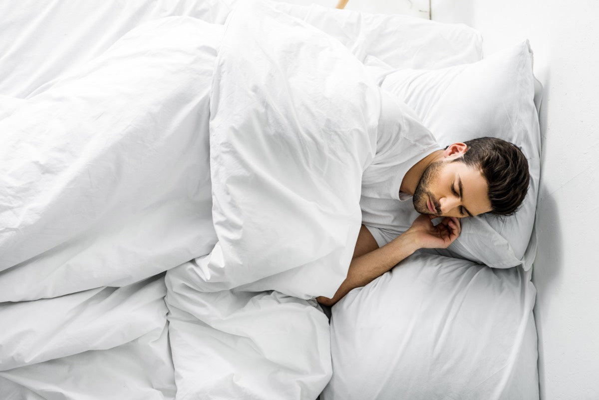 Top view of a young man sleeping in his bed