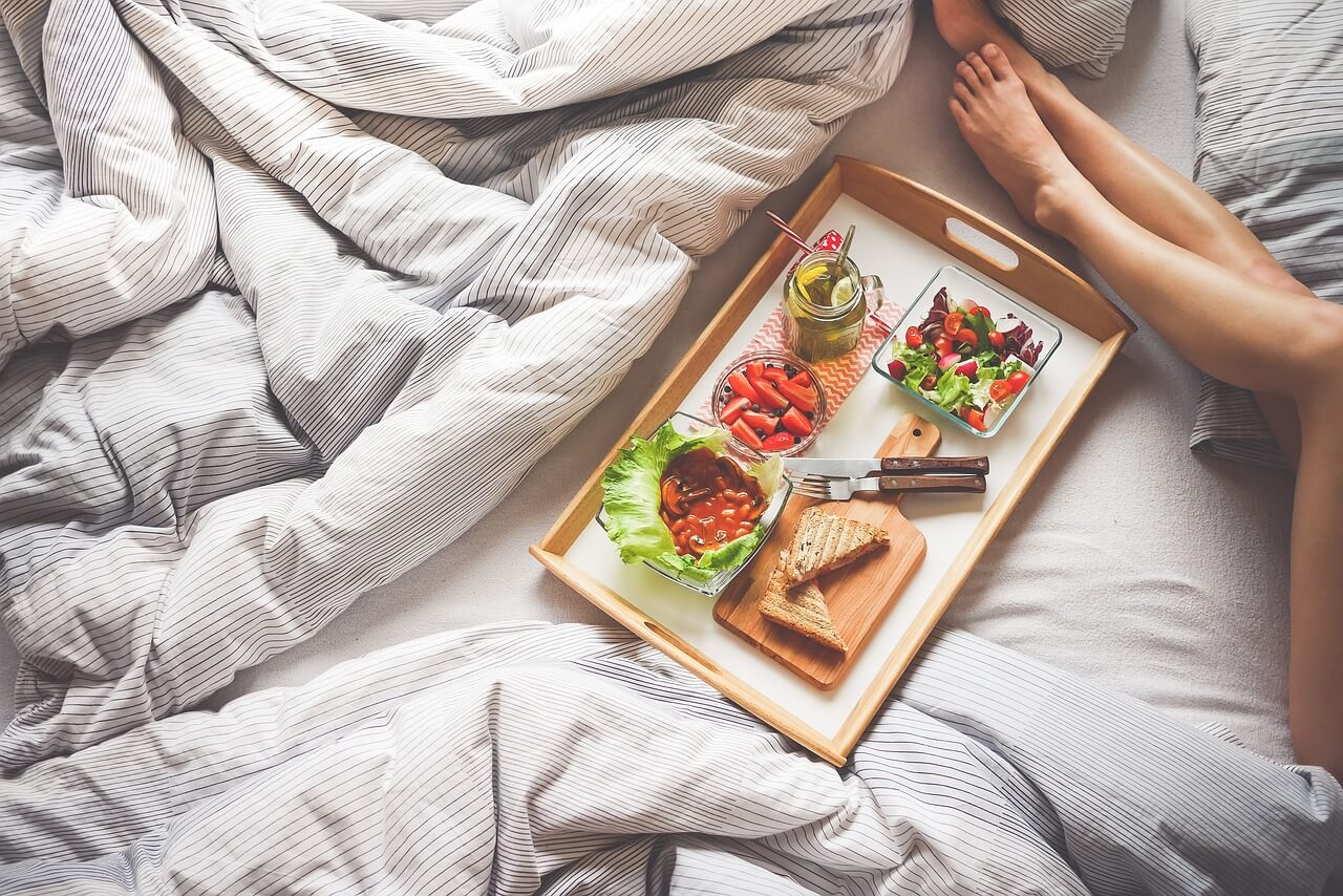 A gourmet platter on a bed among the sheets