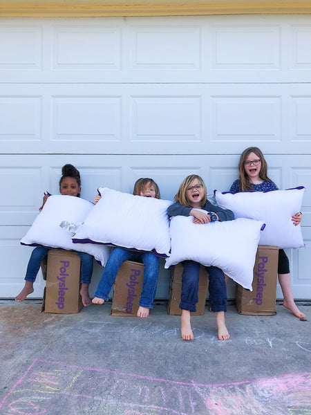 4 kids sitting on delivery boxes hold a Polysleep pillow in their hands