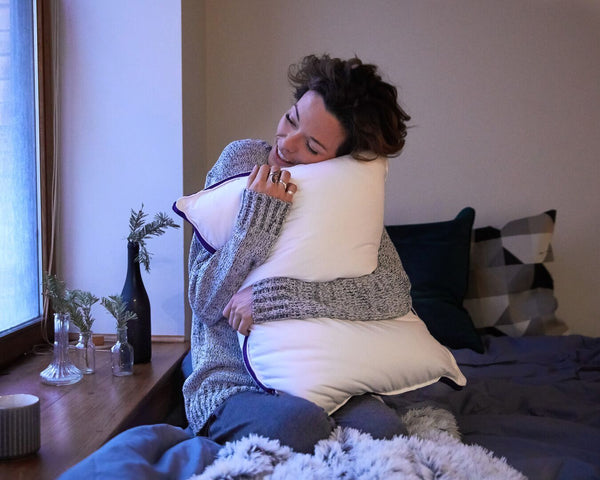 A woman hugs her Polysleep pillow on her bed