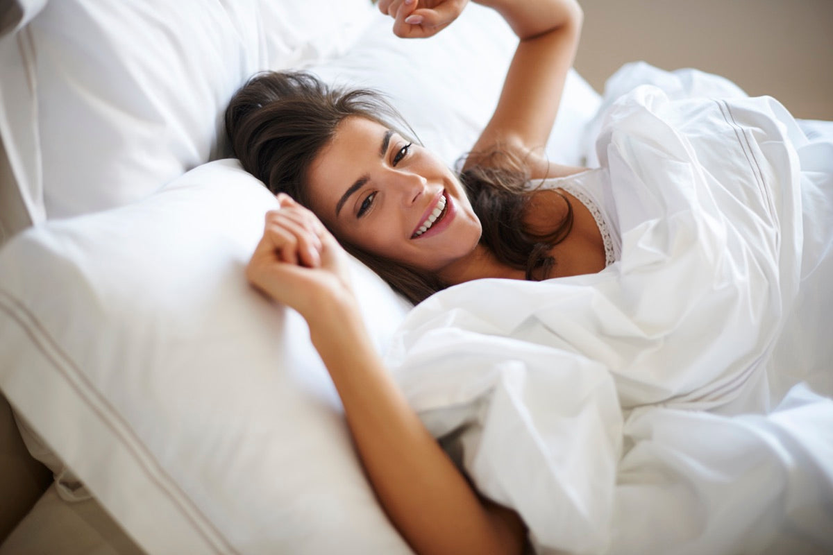 A happy woman lying in her comfortable bed