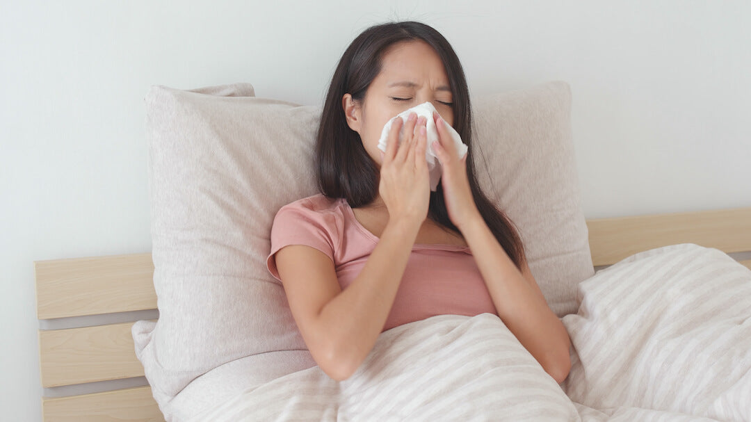 Woman with allergy blowing her nose in bed
