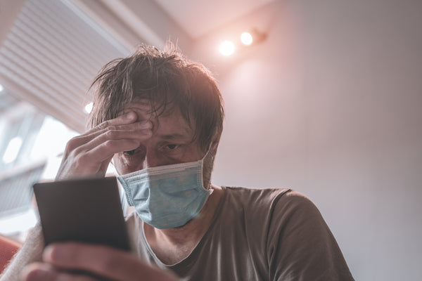 worried man using mobile phone in home quarantine