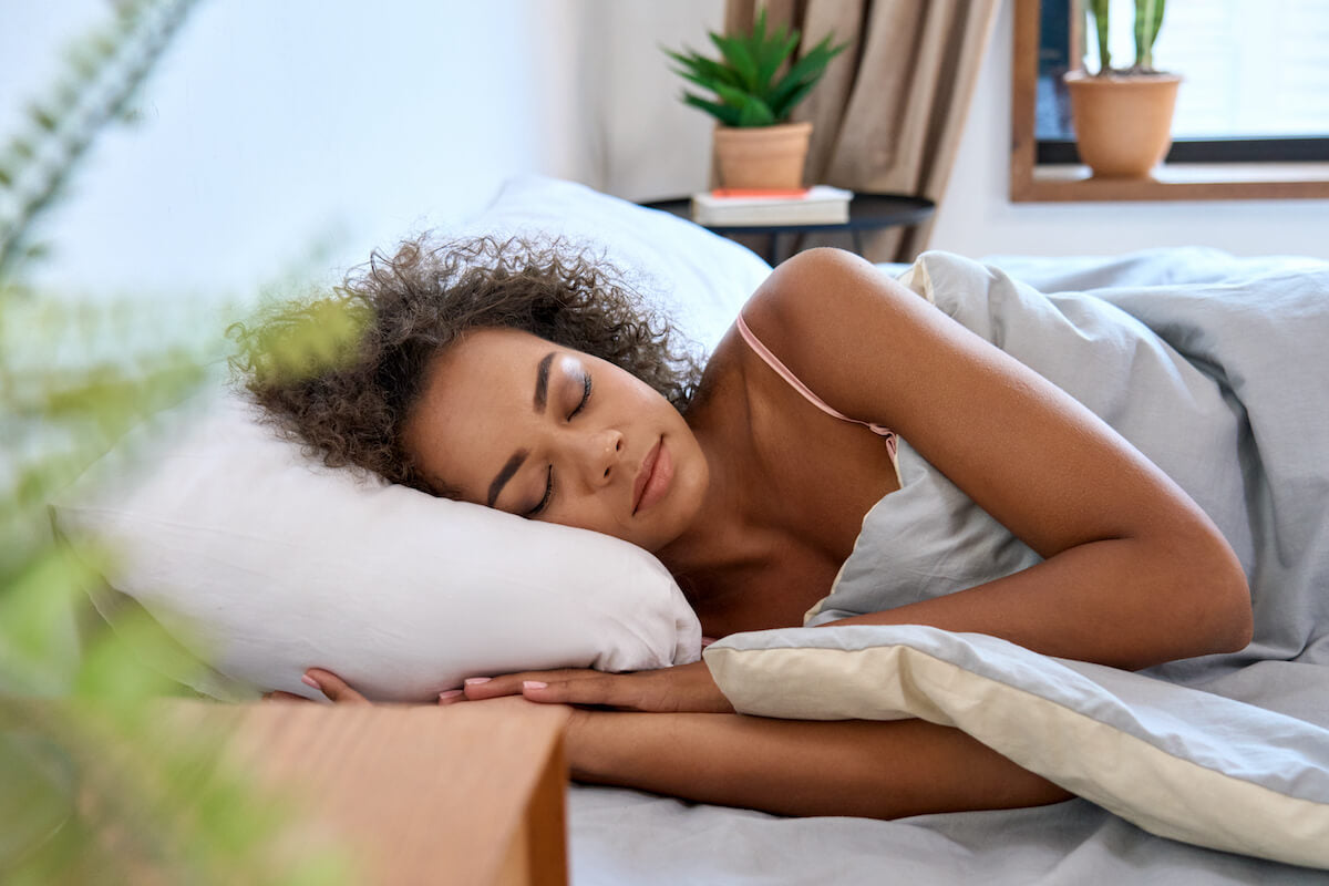 Comfortable young woman sleeping sideways with her head on her pillow