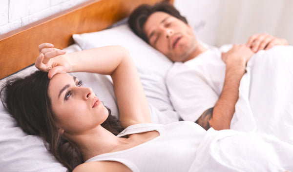young woman suffering from insomnia husband sleeping besides