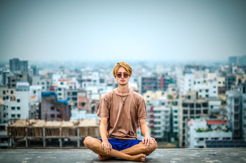 Guy meditating on top of building