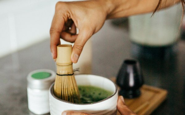 a female hand prepares premium matcha green tea powder by using a bamboo whisk during ceremony
