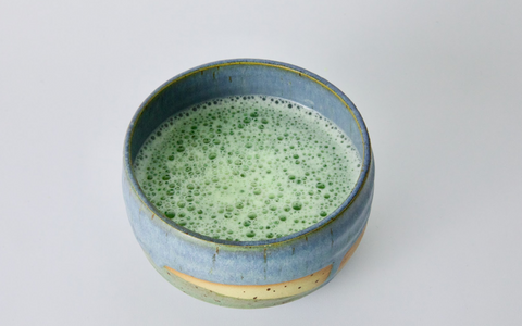 tea ceremony preparation of matcha green tea, super frothy in a blue bowl, white countertop