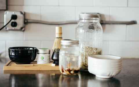 contemporary preparation of matcha green tea using homemade nut milk in a modern kitchen