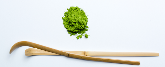 round pile of premium quality matcha with two hand-carved bamboo Japanese tea scoops