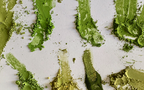 comparison of matcha green teas next to each other during a taste test, on a white piece of paper