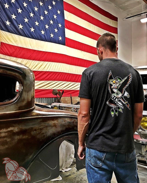 Male with hot rod wearing a tattoo style eagle and pinup shirt in front of American flag.