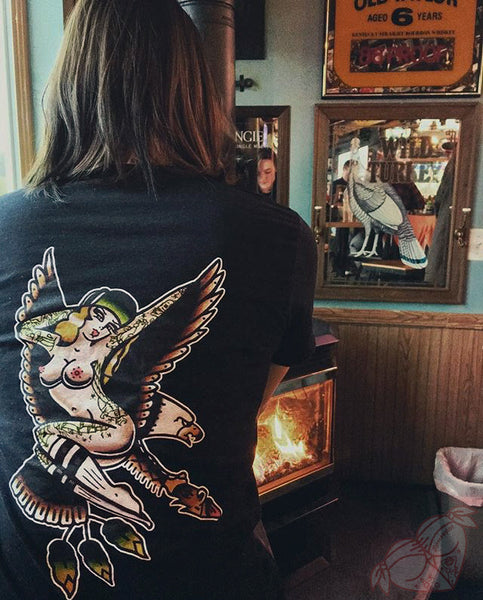 Female in front of wood burning stove wearing a tattoo style eagle and pinup shirt.