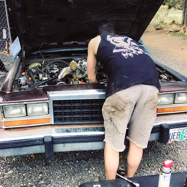 male working on car wearing tattoo style eagle and pinup tank top.