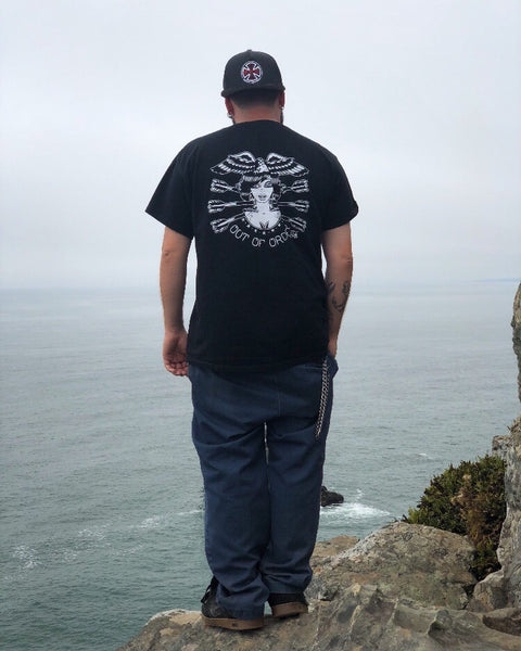 Male wearing tattoo style lady head shirt peering off cliff at ocean.
