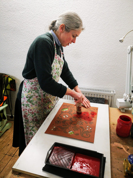 Jane Jeffery applying red paste ink through a stencil