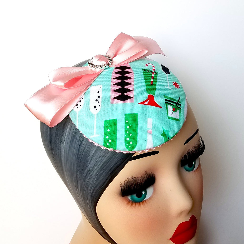 Christmas cocktails pin up  fascinator hat in pink and mint. Mid-century vintage inspired print.