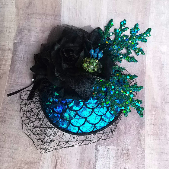 Turquoise and black sparkly glitter mermaid fascinator hat for dapper day or disney bound.