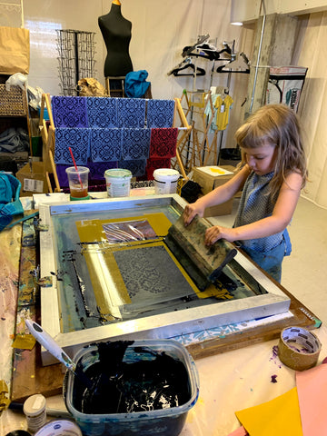 young child learns textile printing in a silkscreen studio